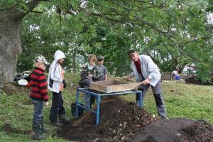Alla åldrar frång bygden hjälper till med utgrävningen